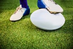 Joueur de rugby posant des pieds sur la boule Photo stock