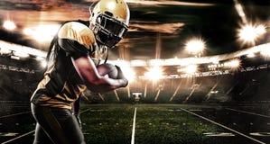 Joueur de sportif de football américain sur le stade fonctionnant dans l'action Papier peint de sport avec le copyspace photo stock