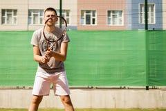Joueur de tennis de débutant de jeune homme faisant des sports sur la cour le jour d'été photographie stock