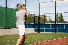 Joueur de tennis de débutant de jeune homme faisant des sports sur la cour le jour d'été photographie stock libre de droits