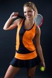Joueur de tennis de l'adolescence sportif de fille avec la raquette sur le noir Images libres de droits