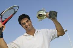 Joueur de tennis masculin soulevant les raquettes de tennis et le portrait de trophée Image libre de droits