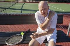 Joueur de tennis masculin supérieur avec douleur d'épaule se reposant sur le banc à la cour Image stock