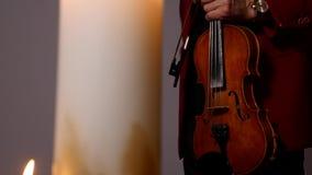 Joueur de violon jouant l'intstrument sur le fond noir avec des bougies clips vidéos
