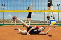 Joueur de volleyball féminin atteignant la boule au sol Image stock