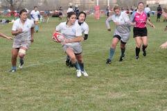 Joueur exécutant avec la bille dans l'allumette de rugby Image libre de droits
