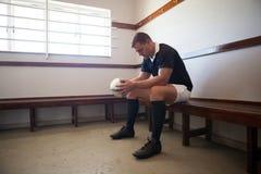 Joueur sérieux avec la boule de rugby se reposant dans la chambre photographie stock