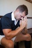 Joueur sérieux de rugby s'asseyant contre le mur image libre de droits