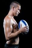 Joueur sans chemise beau réfléchi de sports tenant la boule photographie stock libre de droits