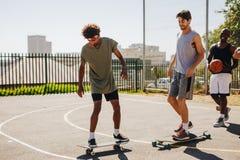 Joueurs de basket patinant sur la planche à roulettes Images libres de droits