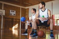 Joueurs de basket réfléchis s'asseyant sur le banc Photos stock