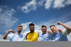 Joueurs de football enthousiastes se tenant ainsi que le bras autour Photo stock