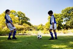 Joueurs de football mignons jouant le football Photos stock