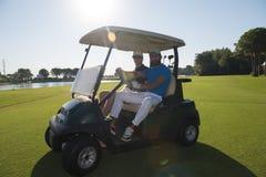 Joueurs de golf conduisant le chariot au cours Images stock