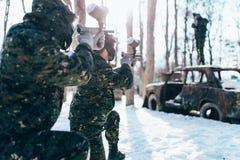 Joueurs de Paintball tirant à l'ennemi, bataille d'hiver photographie stock libre de droits