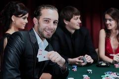 Joueurs de poker s'asseyant autour d'une table à un casino Image stock