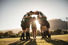 Joueurs de rugby se blottissant sur le champ de sports photos stock