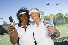 Joueurs de tennis féminins supérieurs avec le trophée prenant l'autoportrait Images stock