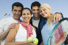 Joueurs de tennis heureux avec des raquettes et boules contre le ciel Image libre de droits