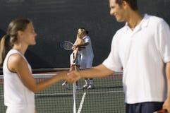 Joueurs de tennis se serrant la main sur la cour Photo stock