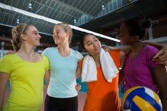 Joueurs féminins de sourire se tenant ainsi que le bras autour Photographie stock libre de droits