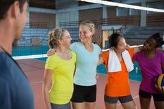 Joueurs féminins de sourire se tenant ainsi que le bras autour Photo libre de droits