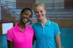 Joueurs féminins de sourire se tenant ensemble dans la cour de volleyball Image libre de droits