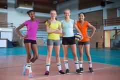 Joueurs féminins de sourire se tenant ensemble dans la cour de volleyball Photographie stock