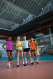 Joueurs féminins de sourire se tenant ensemble dans la cour de volleyball Photo libre de droits