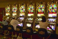 Joueurs mettant des pièces de monnaie dans des machines à sous à Las Vegas, nanovolt Image stock