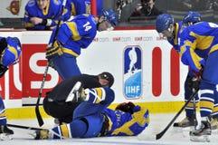 Joueurs pliés au-dessus du joueur de hockey blessé Image libre de droits