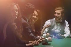 Joueurs s'asseyant à la table jouante dans le casino Photographie stock