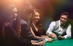 Joueurs s'asseyant à la table jouante dans le casino Photographie stock libre de droits