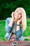 Joueuse de écoute de jeune fille blonde photographie stock libre de droits