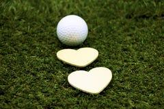 Jouez au golf et avec la forme d'amour sur le fond vert Photographie stock