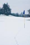 Jouez au golf l'indicateur dans la neige avec des pistes menant à elle photos stock