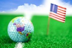 Jouez au golf la boule du monde de globe avec le drapeau des Etats-Unis sur la pelouse ou le champ verte photos libres de droits