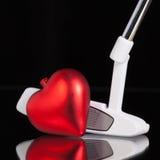 Jouez au golf le putter et le symbole d'amour sur le bureau en verre noir Photos libres de droits