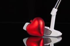Jouez au golf le putter et le symbole d'amour sur le bureau en verre noir Image libre de droits