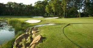 Jouez au golf le vert avec les trappes, l'eau et les arbres Photographie stock libre de droits