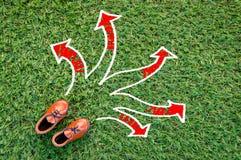 Jouez la chaussure en cuir sur le champ d'herbe avec la flèche jpg Images stock