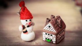 Jouez la maison de bonhomme de neige et de pain d'épice à la table de Noël Image stock