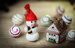 Jouez la maison de bonhomme de neige et de pain d'épice à la table de Noël Photographie stock