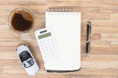 Jouez la voiture avec le carnet, la calculatrice et le café Photo stock