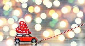 Jouez la voiture fournissant des coeurs pour le jour du ` s de Valentine contre le contexte d'un bokeh coloré Images libres de droits