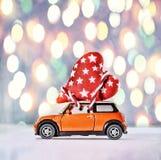 Jouez la voiture fournissant des coeurs pour le jour du ` s de Valentine contre le contexte d'un bokeh coloré Image stock