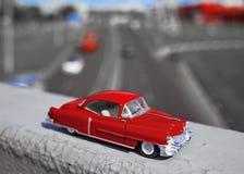 Jouez la voiture rouge sur le fond des routes urbaines Image libre de droits