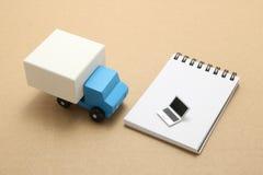 Jouez le camion de voiture et l'ordinateur portable miniature sur le bloc-notes Photographie stock libre de droits