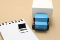 Jouez le camion de voiture et l'ordinateur portable miniature sur le bloc-notes Photographie stock