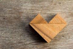 Jouez le puzzle dans la forme de coeur sur le fond en bois Photographie stock libre de droits